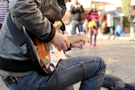 street musician: A street musician plays guitar on the square Stock Photo