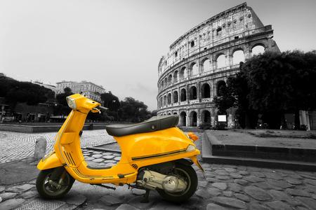 Gele vintage scooter op de achtergrond van Coliseum Stockfoto