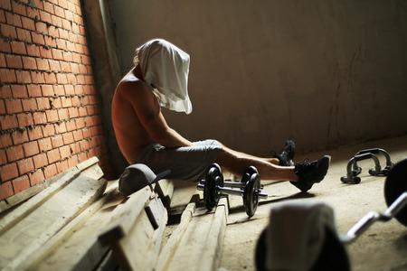 muskeltraining: Kerl sitzt nach dem Training in der Turnhalle