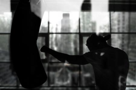 ボクサーは、窓にサンドバッグを打つトレーニング 写真素材