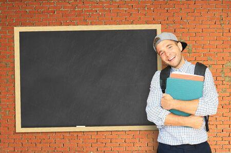estudiantes universitarios: Estudiante con una mochila cerca de los consejos escolares Foto de archivo