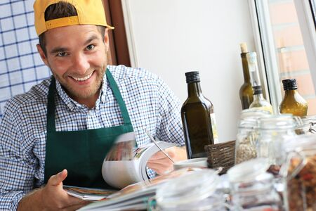 according: Guy cooking the dish according to the recipe Stock Photo