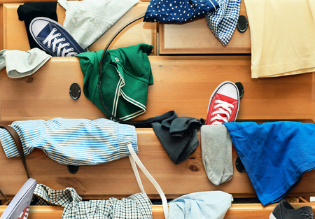 messy clothes: Scattered clothes and shoes in the drawers of the dresser Stock Photo
