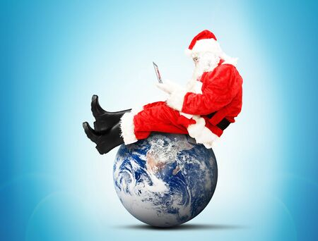 Santa Claus sitting with laptop on the planet
