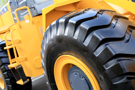 equipment: Large yellow bulldozer with a big wheel