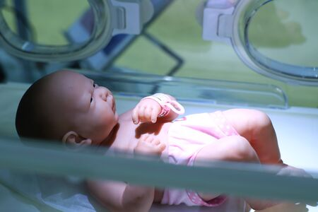 Newborn baby in incubator and medical devices