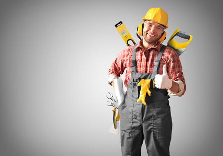 Constructor en el casco amarillo, gafas de protección y ropa de trabajo Foto de archivo