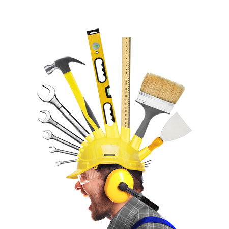 yells: Builder yells in a yellow helmet with a tools Stock Photo