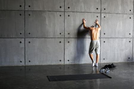 deportista: Hombre en la pared en el gimnasio descansando después del ejercicio Foto de archivo