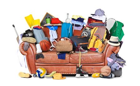 cuarto desordenado: sofá de cuero grande con un montón de cosas diferentes