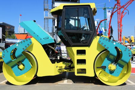 roller compactor: Compactor roller compacting asphalt on a background of construction cranes