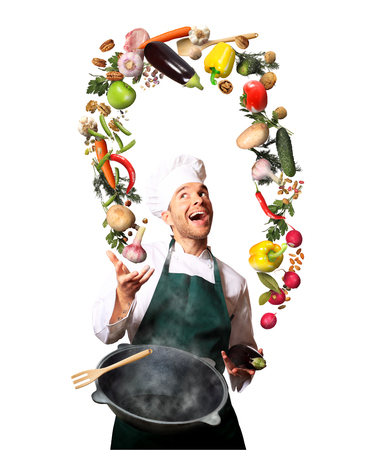 Chef juggling with vegetables and other food in the kitchen Stockfoto