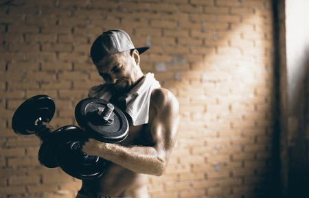 Guy in the baseball cap raises a pair of dumbbells in the gym