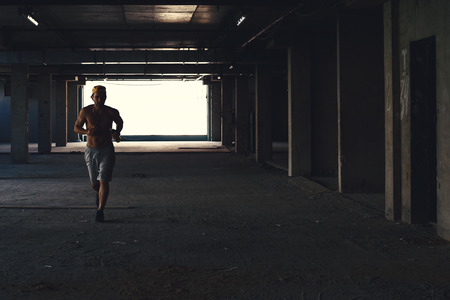 male athlete: Male athlete running on industrial building, fitness