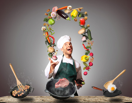 Chef juggling with vegetables and other food in the kitchen Imagens