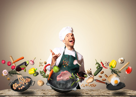 Chef juggling with vegetables and other food in the kitchen Stock Photo