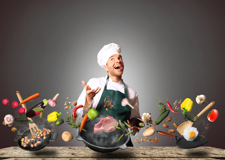 Chef juggling with vegetables and other food in the kitchen Standard-Bild
