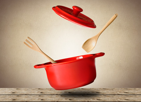 Big red pot for soup with spoon and fork Фото со стока - 65863429