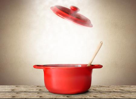 숟가락과 포크가 들어간 스프의 큰 빨간 냄비 스톡 콘텐츠
