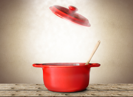 Grote rode pot voor soep met lepel en vork
