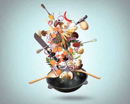 Large iron skillet with falling vegetables and mushrooms