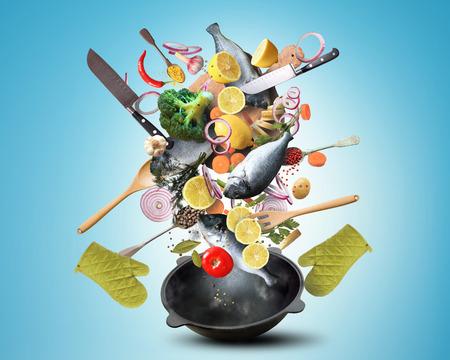 Grande poêle de fer avec la chute des légumes et du poisson Banque d'images