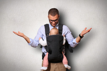 baby carrier: Father holds a baby in a bag