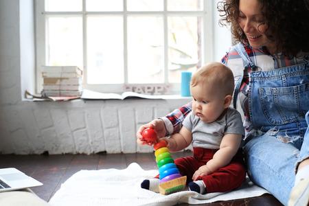 Mutter und kleines Kind spielen im Haus Standard-Bild - 69023127