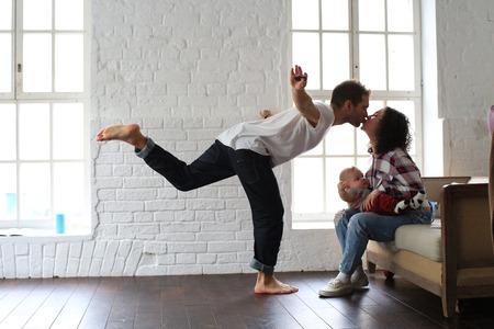 Jonge gelukkige familie ontspannen thuis voor venster