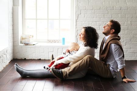 Junge glückliche Familie auf dem Boden zu Hause entspannen