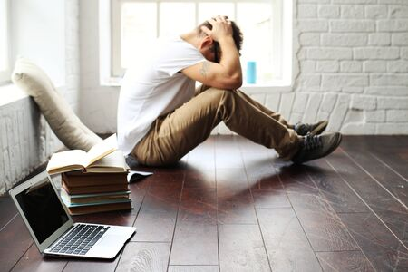 Man upset while working on the laptop at home Stock Photo