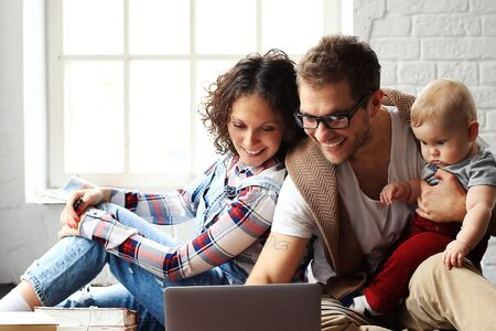 familias felices: Joven familia feliz descansando en su casa en el piso