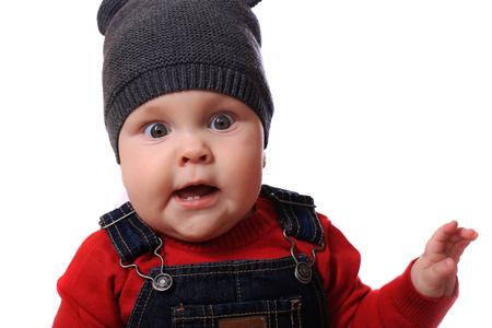massage enfant: Bébé dans le chapeau en souriant alors qu'il était assis dans son lit Banque d'images