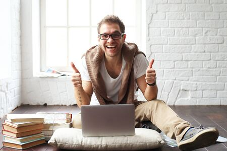 business lifestyle: Young man smiling in front of the laptop