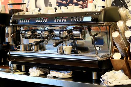 Grote koffiezetapparaat bereidt koffie en kleine kopjes voor
