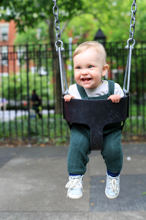 Little boy in overalls on the swing in the park Фото со стока