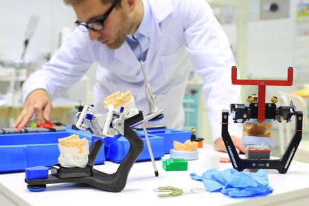 Odontotecnico controlla il suo lavoro in laboratorio