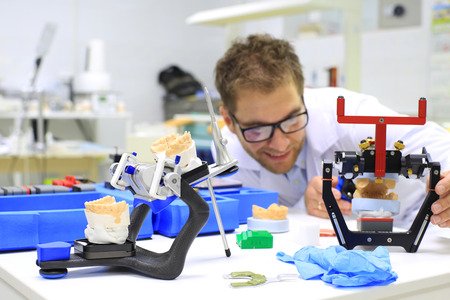 Dental technician checks his work in the lab Standard-Bild