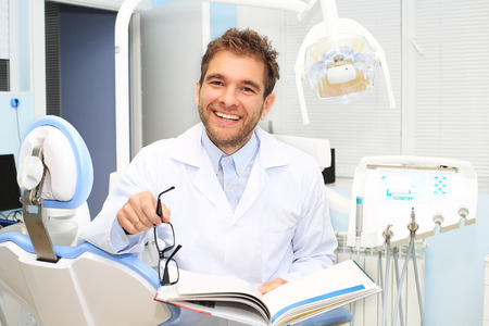 Dentist writes a patient a prescription in medical office photo