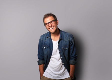 Young man in a denim shirt is smiling photo