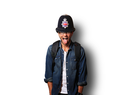 Young man in a helmet of the British policeman stick out his tongue