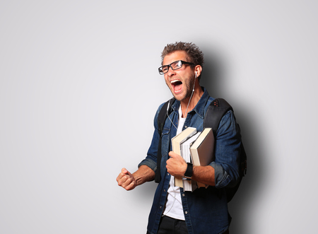 Student wearing glasses and a denim shirt with a bunch of books Stock Photo