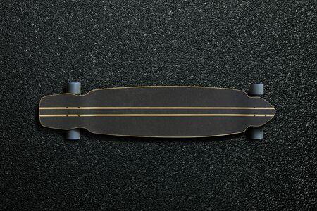 Long skateboard with stripes on the asphalt road Фото со стока