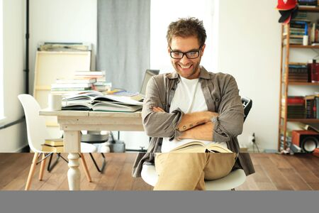 Young man reading book on the background of the desktop Imagens