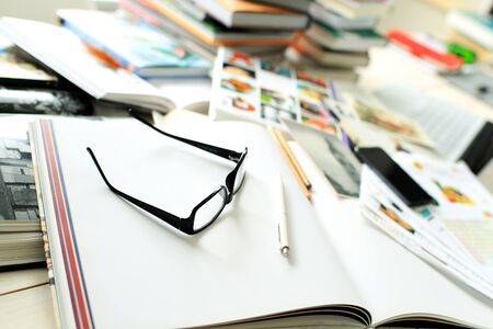 Stack of books on the desktop, and glasses