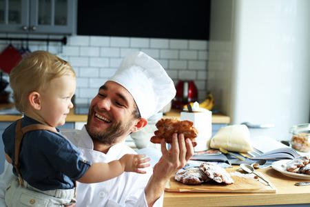 彼の若い息子と一緒にクロワッサンを焼くお父さん