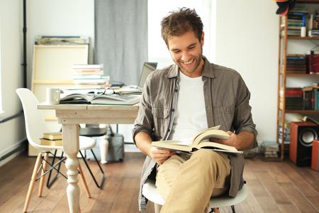 デスクトップの背景に本を読む若い男