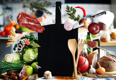 Kitchen a large black board with vegetables and bread Imagens