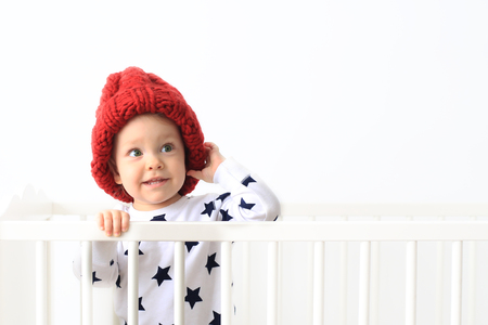 Little boy in a big knitted hat in bed Imagens