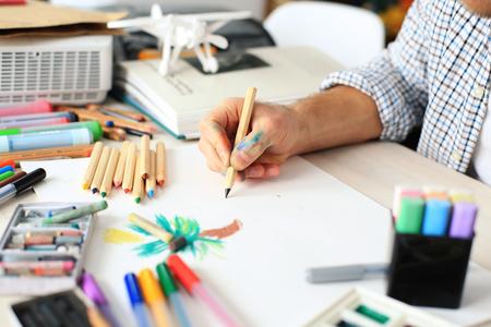 Mann zeichnet mit einem Bleistift auf weißem Papier